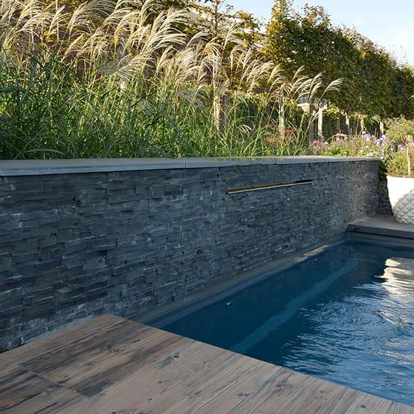 Muur natuurstenen elementen bij strak zwembad